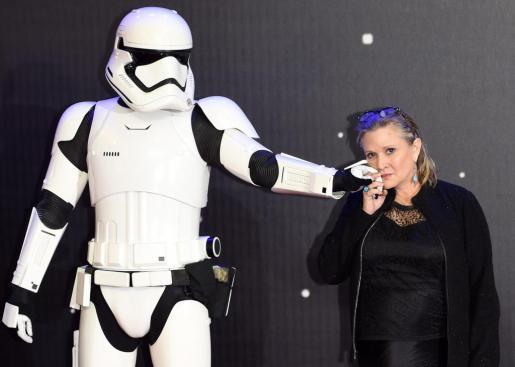 La actriz Carrie Fisher, que ha fallecido este martes tras sufrir un ataque al corazón el pasado viernes, posa junto a un soldado de asalto de la saga de 'Star Wars'.