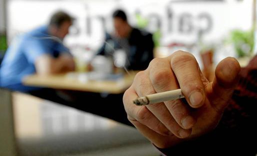 Una mano sostiene un cigarrillo en el interior de un bar, imagen habitual hasta la ley antitabaco de 2011.