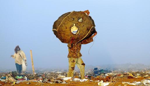 Imagen de un hombre que lleva sobre sus hombros un fardo de basura recogido en un vertedero de Managua.