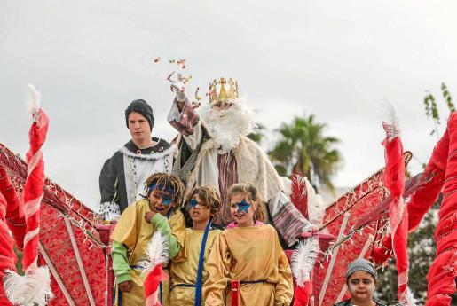 El rey Melchor, montado en una carroza junto a su comitiva, lanza caramelos a los niños que estaban esperando su llegada en la localidad de Jesús. Foto: TONI ESCOBAR