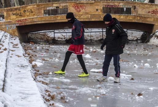 Dos jóvenes cruzan un lago congelado en un parque de Skopje, Macedonia.