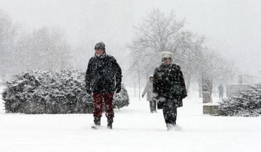 Varias personas caminan por la nieve en Belgrado.