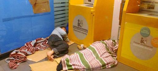 Imagen de archivo de dos personas sin techo durmiendo junto a los cajeros automáticos de una entidad bancaria.