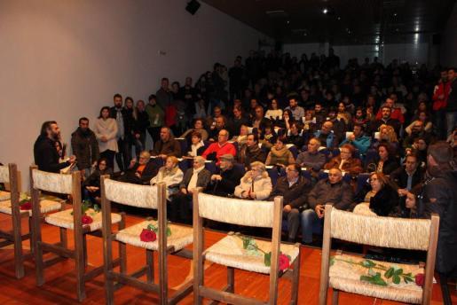 Las sillas y las rosas presidieron el escenario del auditorio, que se llenó por completo durante el homenaje.