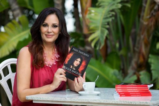 La modelo Nati Expósito, posando con su novela titulada 'Pocos ángeles y muchos demonios'.