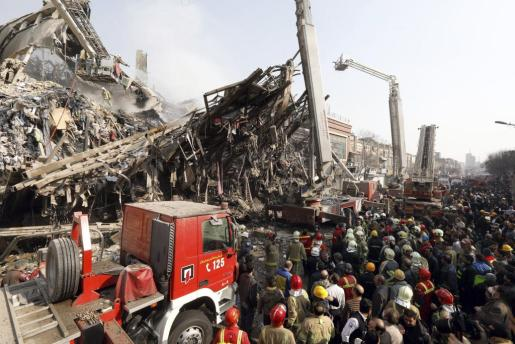 Miembros de los servicios de rescate iraníes frente a los escombros del edificio Plasco después de que se derrumbase como consecuencia de un grave incendio.