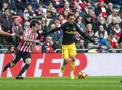 El defensa del Athletic Club de Bilbao Iñigo Lekue (i) disputa un baló con el delantero francés del Atlético de Madrid Antoine Griezmann (d).