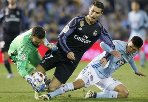 El delantero portugués del Real Madrid, Cristiano Ronaldo cae ante los jugadores del Celta de Vigo, el guardameta Sergio Álvarez y el defensa argentino Facundo Roncaglia.