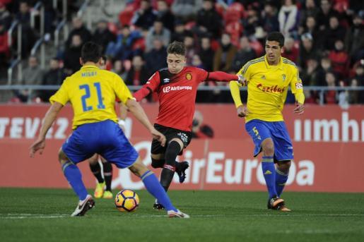 Brandon conduce el balón ante dos jugadores del Cádiz en Son Moix.