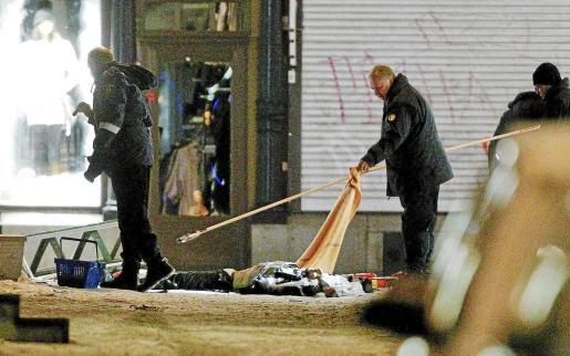 Agentes de la policía forense examinan los restos del supuesto terrorista, en pleno centro de Estocolmo.
