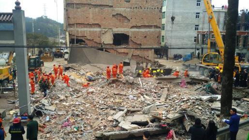Numerosos trabajadores intentan rescatar a los atrapados tras el derrumbe de cuatro edificios en una zona de China.