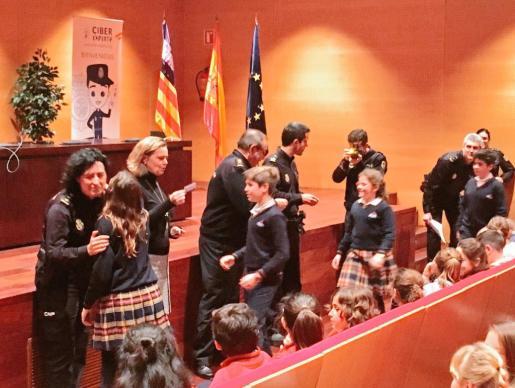 En la imagen, la delegada del Govern, María Salom junto al cuerpo de la Policía Nacional, entregando el carné a los menores que les acredita como «ciberexperto».