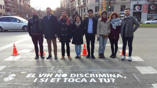 El alcalde, los regidores y miembros de Taula per la Sida ante uno de los lemas pintados en un paso de peatones.