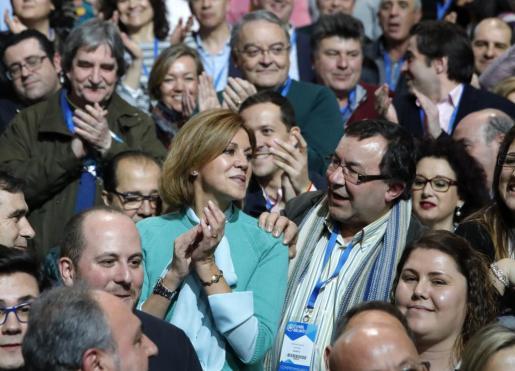 La secretaria general del PP, María Dolores de Cospedal, aplaude tras la primera jornada del XVIII congreso nacional del PP que se ha inaugurado la tarde de este viernes en la Caja Mágica de Madrid.