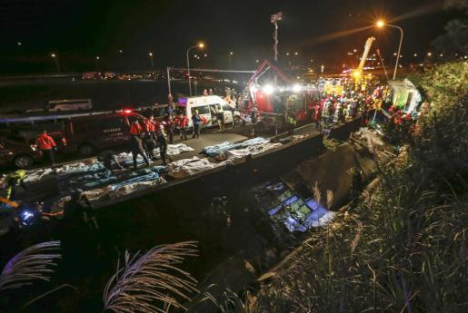 Los cuerpos de las víctimas mortales de un accidente de autobús turístico son alineados en una autopista de Taipei, Taiwán.