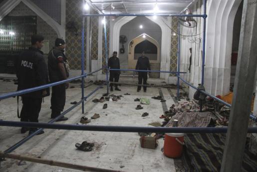 Oficiales de seguridad inspeccionan el templo sufí donde se ha producido un ataque suicida durante la hora del rezo en Sehwan, Pakistán.