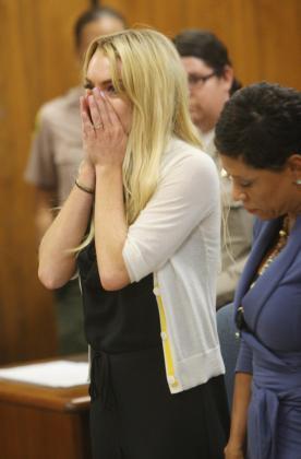 La actriz estadounidense Lindsay Lohan (i) llorando al escuchar su sentencia en un juzgado en Beverly Hills, California, el pasado mes de julio.