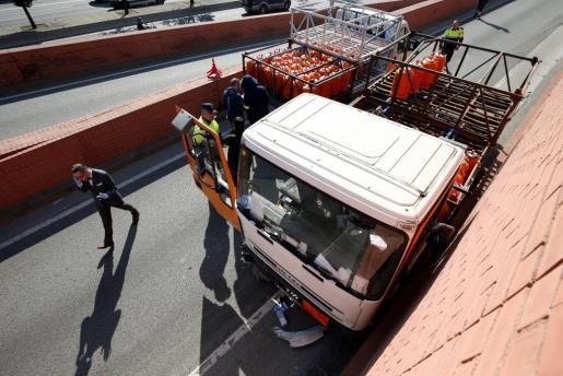 Agentes de policía inspeccionan el camión robado por el detenido.