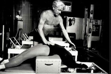 Imagen de Joseph Pilates, ayudando a una mujer a realizar sus ejercicios.
