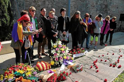 Los asistentes arrojan claveles rojos durante la ofrenda floral en el cementerio.