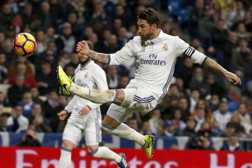El defensa del Real Madrid, Sergio Ramos, golpea el balón durante el encuentro correspondiente a la jornada 25 de Primera División, que han disputado esta noche frente a la UD Las Palmas en el estadio Santiago Bernabéu, en Madrid.