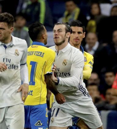 El galés del Real Madrid Gareth Bale (d) empuja a Jonathan Viera, de la UD Las Palmas, por lo que vio cartulina roja, durante el encuentro correspondiente a la jornada 25 de Primera División.