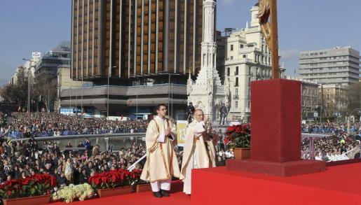 El cardenal arzobispo de Madrid, Antonio María Rouco Varela (d), consagra la hostia durante la Misa de la Sagrada Familia que ha tenido lugar hoy en la Plaza de Colón de Madrid.