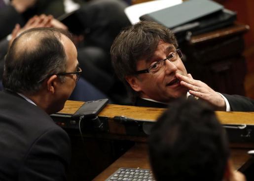 El presidente de la Generalitat, Carles Puigdemont, conversa con el portavoz de JxS, Jordi Turull (i), durante la sesión de control al gobierno catalán que se ha celebrado este miércoles por la mañana en el Parlament de Cataluña.