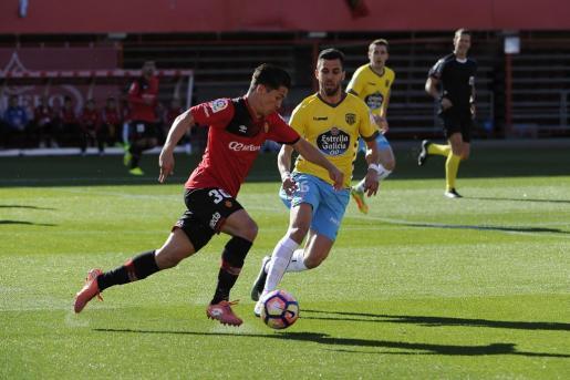 Juanjo Nieto conduce el balón ante la presión de un jugador del Lugo.