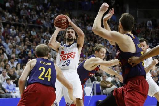 El base del Real Madrid, Sergio Llull (2i), lanza a canasta ante la defensa del jugador estadounidense del FC Barcelona Lassa, Bradley Scott Oleson, durante el encuentro correspondiente a la jornada 24 de la liga ACB, que han disputado en el Palacio de los Deportes de Madrid.