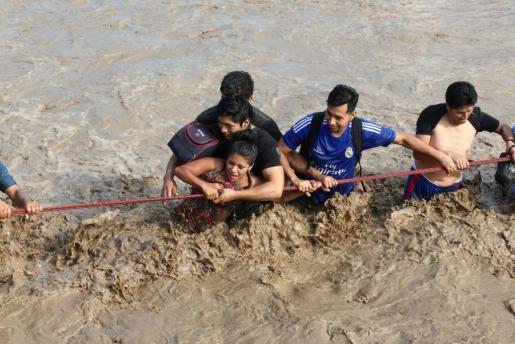 Los servicios de emergencias ayudan a una mujer a cruzar un río desbordado por las inundaciones.