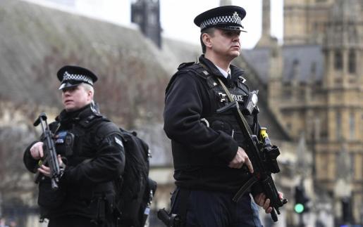 Agentes de policía británicos permanecen en guardia tras un tiroteo ante el Parlamento en Londres.