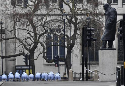 Agentes de la Policía Científica buscan pruebas en la Plaza del Parlamento, junto a la sede de la Cámara británica.