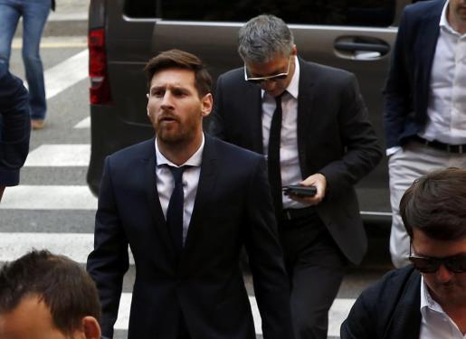 El jugador del FC Barcelona Lionel Messi (c) y su padre, Jorge Horacio Messi (detrás), a su salida de la Audiencia de Barcelona tras declarar en la tercera jornada del juicio por tres delitos contra la Hacienda Pública.