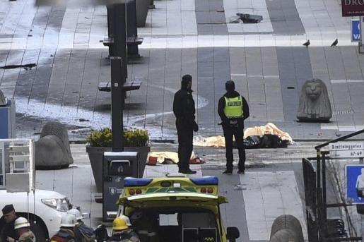 La policía custodia el cuerpo de una de las víctimas del atentado en el centro de Estocolmo.