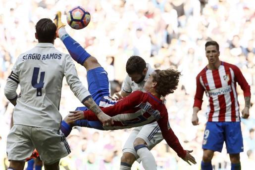 El delantero francés del Atlético de Madrid, Antoine Griezmann (c) intenta un remate de chihlena durante el partido.