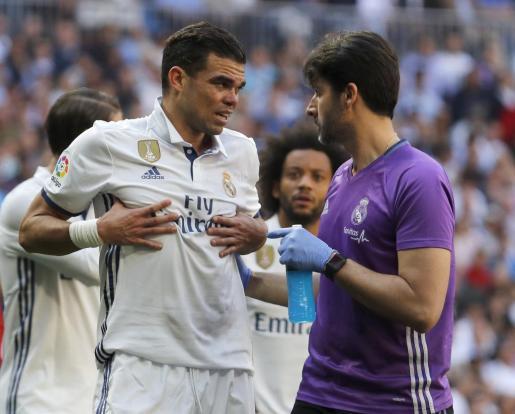 El defensa portugués del Real Madrid Pepe (i) recibe asistencia médica tras lesionarse durante el partido ante el Atlético de Madrid.