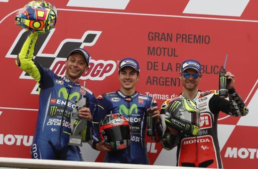 El piloto español Mavericks Viñales (C) de Yamaha celebra en el podio su victoria junto al segundo puesto, el italiano Valentino Rossi (i) de Yamaha, y el tercer puesto, británico Cal Crutchlow (d) de Honda.