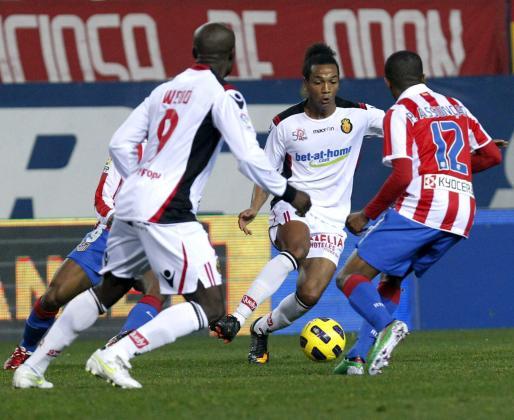 El delantero del Real Mallorca Emilio Nsué (c) pelea un balón con el centrocampista brasileño del Atlético de Madrid, Paulo Assunçao (d), durante el partido correspondiente a la decimonovena jornada de liga.