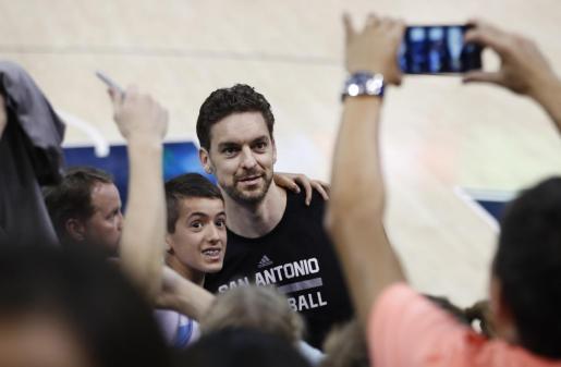 El jugador de San Antonio Spurs, el español Pau Gasol (c), posa para un fotografía junto a un aficionado.
