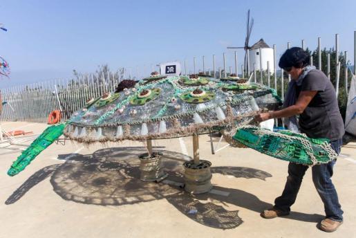 Una de las artistas remacha su escultura realizada con materiales reciclados. Foto: DANIEL ESPINOSA