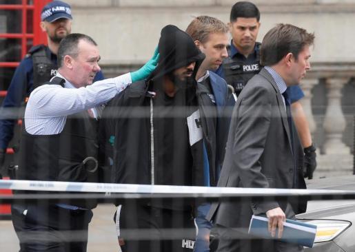 Imágenes del arrestado mientras es conducido por agentes de la policía.