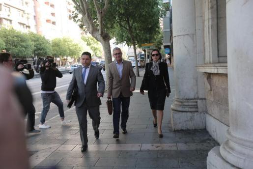 Xavier Busquets, en el centro, llegando a los juzgados en compañía de su abogado Andreu Rotger.