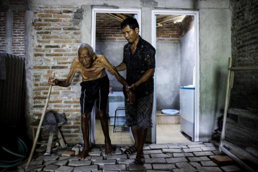 En la imagen, el hombre de 146 años, conocido como Mbah Gotho, caminando junto a su nieto Suryanto, de 47 años, en su casa, en Indonesia.
