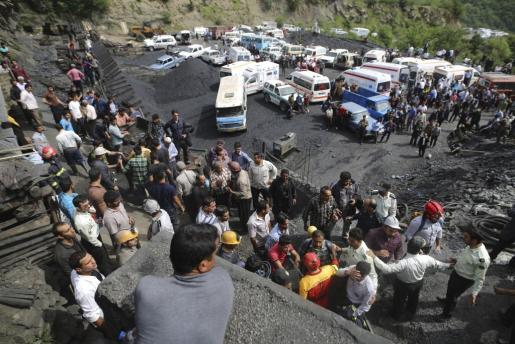 Personal de emergencias iraní y varios mineros transportan a los heridos en una explosión en una mina de carbón.