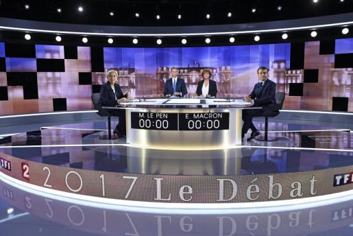 La candidata ultraderechista a la presidencia de Francia por el Frente Nacional, Marine Le Pen (i), y su rival, el socioliberal del movimiento En Marche !, Emmanuel Macron (d), junto a los periodistas Christophe Jakubyszyn (2i) y Nathalie Saint-Cricq (d).