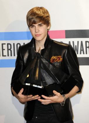 El cantante canadiense Justin Bieber posa con los premios a artista revelación favorito y Artista pop/rock masculino Favorito en la sala de prensa durante la 38 edición de entrega de los American Music Awards.
