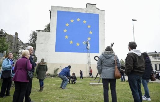 Varios curiosos observando el mural sobre el 'brexit' del artista Banksy que ha aparecido en la fachada lateral de un edificio en Dover (Reino Unido).