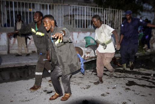 Varias personas ayudan a los heridos tras la explosión de un coche bomba en la puerta de un restaurante de Mogadiscio, Somalia.