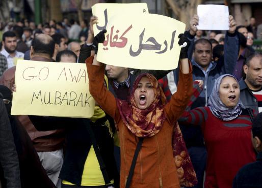 """Egipcios sostienen unas pancartas, en las que se lee """"Véte, es suficiente"""" (c) durante las manifestaciones y concentraciones producidas en el centro de El Cairo, Egipto, hoy, domingo 30 de enero de 2011."""
